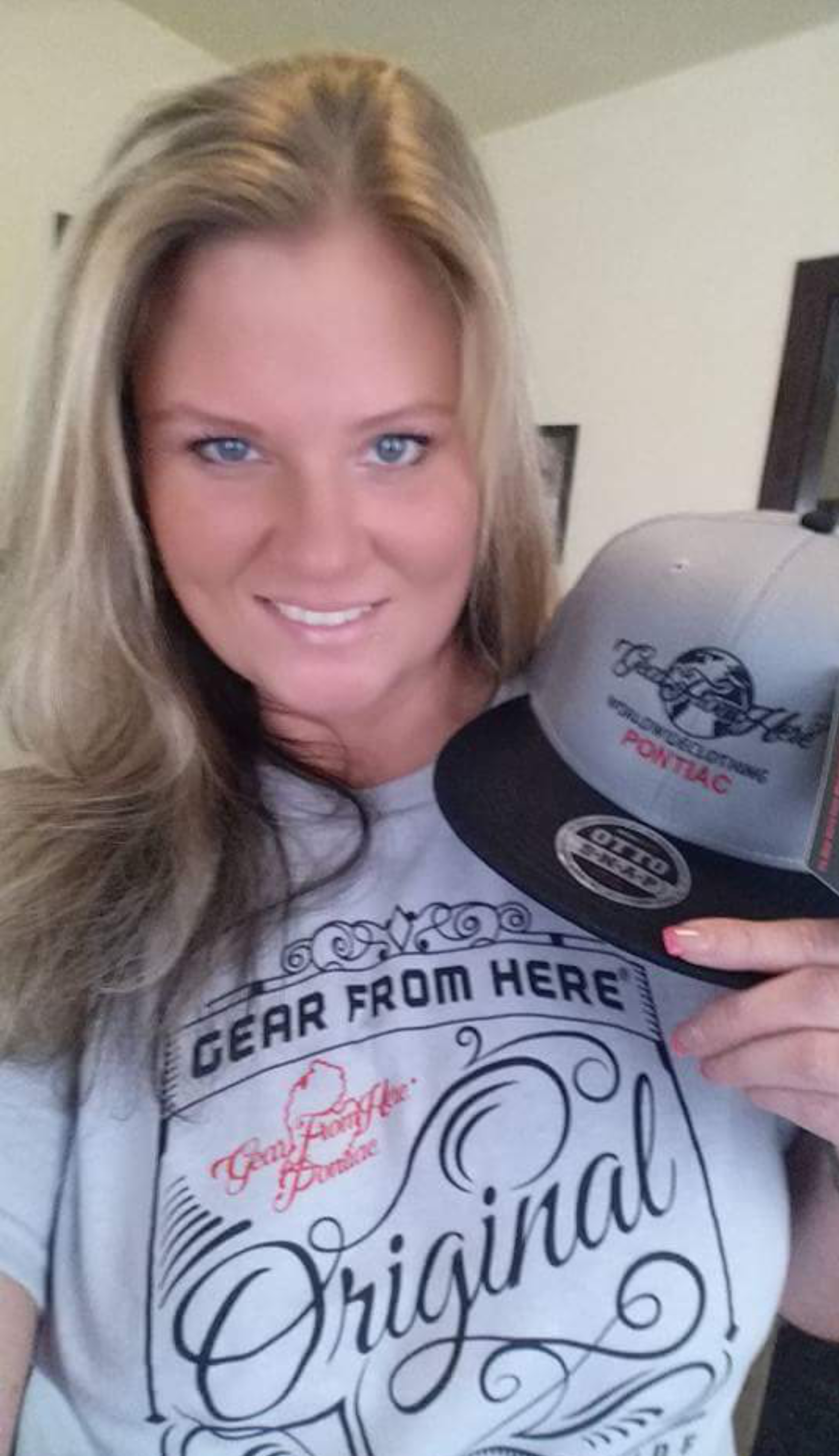 Woman wearing gray Original t-shirt and holding Pontiac hat